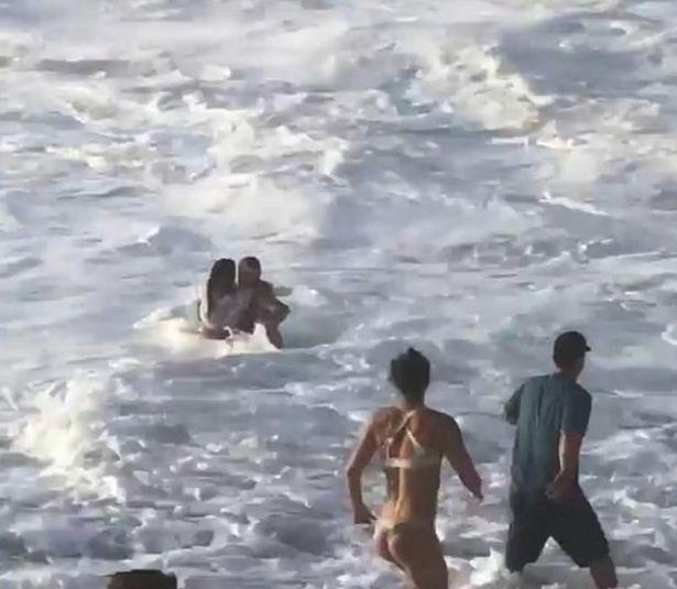 Surfista profissional salva mulher que estava se afogando e presa entre rochas afiadas e ondas enormes